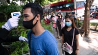 An officer checks the temperature of people wearing face masks to help curb the spread of the coronavirus as they line up at…