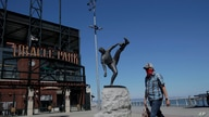 The statue of Hall of Fame pitcher Juan Marichal is shown behind a man wearing a mask outside of Oracle Park, the San Francisco…