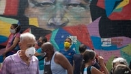 Pedestrians wearing protective face masks as a precaution against the spread of COVID-19, walk past a mural featuring the eyes…