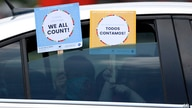 FILE - In this June 25, 2020, file photo, two young children hold signs through the car window that make reference to the 2020…