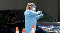 A healthcare worker puts a test swab into a vial after testing a passenger at a drive-through coronavirus testing site outside…