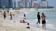 Beach goers walk along the shore on Miami Beach, Florida's famed South Beach, Tuesday, July 7, 2020. Beaches in Miami-Dade…