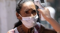 A woman eyes a healthcare worker as she has her body temperature measured as a precaution against the spread of the new…