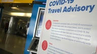 A sign warns airline passengers about a travel advisory that applies to people arriving from certain states at Newark Liberty…