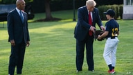 Former New York Yankees Hall of Fame pitcher Mariano Rivera looks on as President Donald Trump is handed a baseball glove as he…