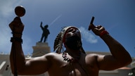 Gypsy Cordova blows smoke and shakes a maraca in front of a Juan Ponce de Leon monument while leading a group of activists in a…