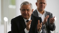 Mexico's President Andres Manuel Lopez Obrador, left, applauds prior to delivering a speech during his visit to a public…