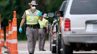 A Texas Department of Public Safety State Trooper directs traffic at a checkpoint in Orange, Texas, near the Louisiana state…