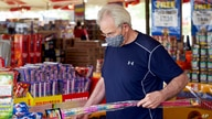 A man wears a face mask as he shops for fireworks for his grandchildren, at Wild Willy's Fireworks tent in Omaha, Neb., Monday,…