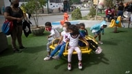 Children wearing protective face masks ride a merry go round in a park in Caracas, Venezuela, Friday, July 17, 2020, amid the…