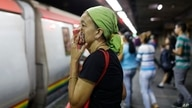 A woman covers her mouth and nose with a wash cloth on a subway platform in Caracas, Venezuela, Friday, March 13, 2020…