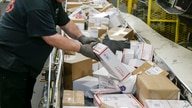 Steve Robino arranges packages on a conveyor belt at the main post office in Omaha, Neb., Thursday, Dec. 14, 2017. Postal…