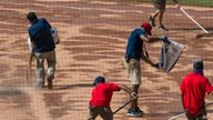 Grounds crew members prepare the rain-soaked field for the resumption of the rain-delayed baseball game between the Washington…