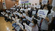 Anti-war activists hold cards after a press conference to demand the peace on the Korean peninsula on the eve of the 70th…