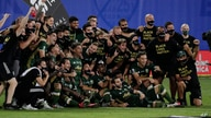 Portland Timbers players pose for photos after defeating Orlando City 2-1, during an MLS soccer tournament, Tuesday, Aug. 11,…