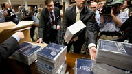 FILE - In this April 10, 2013, file photo, copies of President Barack  Obama's budget plan for fiscal year 2014 are distributed…