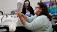 Miami-Dade County Department of Elections employee Elizabeth Prieto gathers vote-by-mail ballots for the August 18 primary…