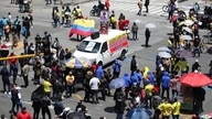 People block an intersection to protest for the right to work during partial lockdowns implemented by Mayor Claudia Lopez to…