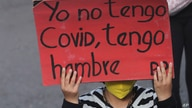 """A woman holds a sign that reads in English """"I don't have COVID, I'm hungry"""" during an anti-government march. in Quito, Ecuador,…"""