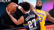 Denver Nuggets' Jamal Murray (27) drives against Los Angeles Lakers' LeBron James (23) and scores during the first half of an…