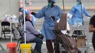 FILE - In this Monday, July 6, 2020 file photo, a health care worker administers a COVID-19 test at a site sponsored by…