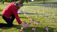House Speaker Nancy Pelosi kneels to look at small flags placed on the grounds of the National Mall by activists from the COVID…