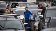 People stand outside their vehicles as they wait in a line near a gas station to fill their tanks in Caracas, Venezuela,…