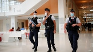 French Police officers patrol in the hall of the Paris courthouse on the second day of the 2015 attacks trial, Thursday, Sept…