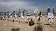 An Afghan young boy site near to the grave of his classmate, adorned with his picture, on the outskirts of Kabul, Afghanistan,…