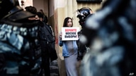 """FILE - In thisSaturday, Aug. 10, 2019 file photo, A woman holds a poster reading """"Give us back our elections in Moscow!"""" in…"""