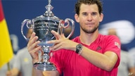 Dominic Thiem, of Austria, holds up the championship trophy after defeating Alexander Zverev, of Germany, in the men's singles…