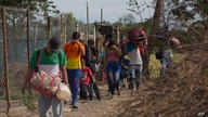 """In this Aug. 31, 2018 photo, Venezuelans illegally cross into Colombia, to Villa del Rosario, along a path known as a """"trocha.""""…"""