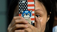 A woman takes a photo with a phone that has a United States flag themed cover outside the United States Consulate in Chengdu in…
