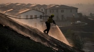 Firefighter Tylor Gilbert puts out hotspots while battling the Silverado Fire, Monday, Oct. 26, 2020, in Irvine, Calif. A fast…