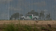 U.S. Customs and Border Patrol vehicle moves along the Fisher border wall, a privately funded border fence, along the Rio…