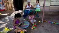 In this Nov. 4, 2013 photo, Evelina Gonzalez is with her daughter Evelin while her two nieces play nearby at her home in…