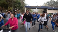 Migrants walk past a customs checkpoint as they enter Guatemala, near Agua Caliente, after crossing the border with Honduras,…