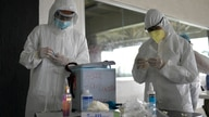 Healthcare workers prepare to take nasal swab samples to test for COVID-19, at the Cocodrilos Sports Park in Caracas, Venezuela…