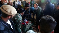 Relatives stand around the dead body of a boy who was killed by a mortar shell attack in Kabul, Afghanistan, Saturday, Nov. 21,…