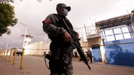 A Civil National Police officer stands guard on the perimeters of a maximum security prison in Izalco, El Salvador, Friday,…