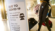 A sign displaying COVID-19 prevention protocols stands beside the passenger drop-off area as travelers arrive at Terminal C at…