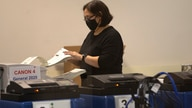 A. poll worker scans ballots at the Maricopa County Recorders Office where votes in the general election are being counted, in…
