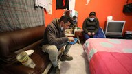 Venezuelan migrant Yaquelin Timaure, right, accompanies her partner Richard Luzardo, while he has lunch at their home in Bogota…