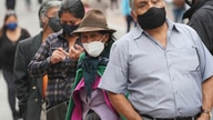 People wearing masks to curb the spread of the new coronavirus, line up outside a bank in Quito, Ecuador, Tuesday, Dec. 8, 2020…