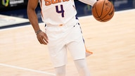 Phoenix Suns guard Jevon Carter (4) dribbles the ball during the first half of an NBA basketball game against the Washington…
