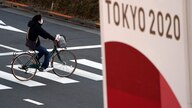 A man wearing a protective mask to help curb the spread of the coronavirus rides a bicycle near a banner of the Tokyo 2020…