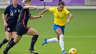 Brazil forward Debinha (9) controls a ball in front of United States defenders Emily Sonnett (14) and Abby Dahlkemper (7)…