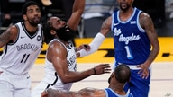 Brooklyn Nets guard James Harden, center left, shoots as he is fouled by Los Angeles Lakers forward LeBron James (23) during…