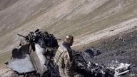 In this photo released by Armenian Foreign Ministry on Wednesday, Sept. 30, 2020, a soldier stands near the wreckage of an…