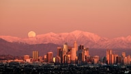 The moon rises over snow covered mountains, behind the downtown Los Angeles skyline, viewed from Kenneth Hahn State Recreation…